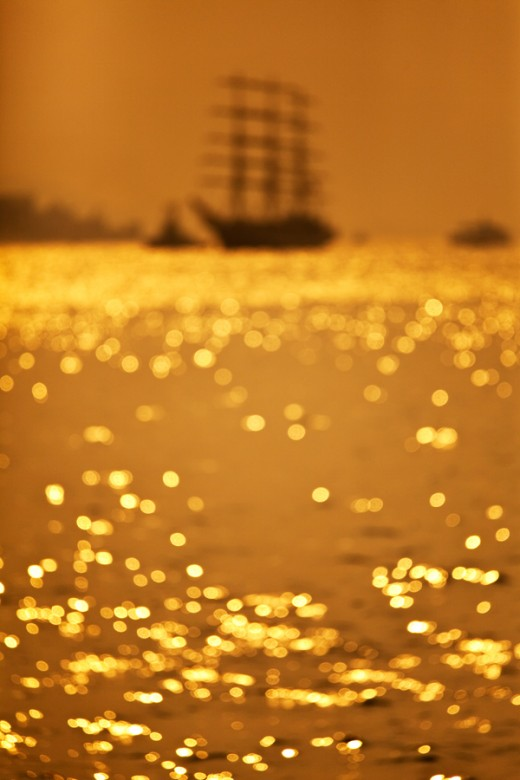 The lens bokeh made a mysterious sence of the classic boat under the golden evening in Victoria Harbour